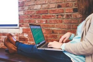 Woman sitting on ledge in brown boots with laptop on lap searching for the meaning of what a scopist is