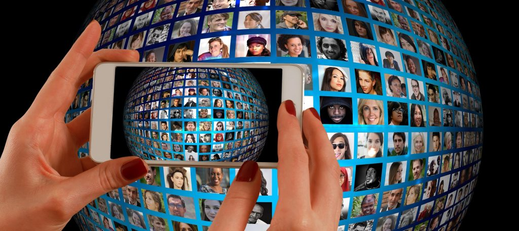 woman's hand holding phone taking photo of a globe with people's faces on it for how to become a scopist