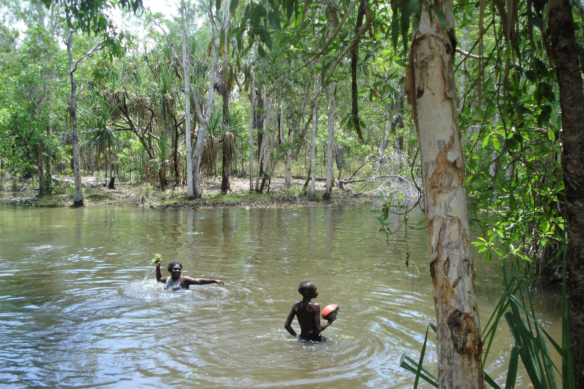 Two young people playing in a water hole in the jungle of Bathurst Island