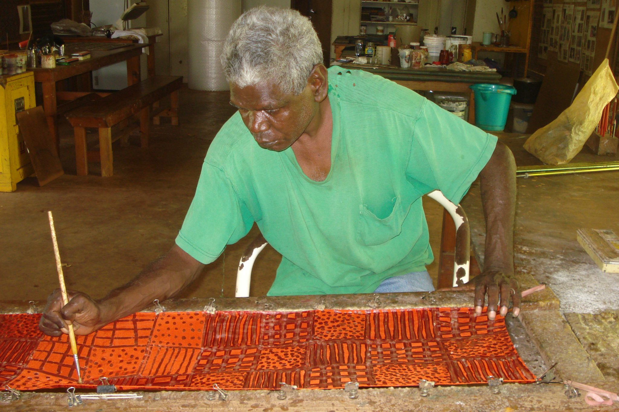 Male artist wearing a lime green T-shirt and painting red and orange on a canvas on a table on my Tiwi Islands tour