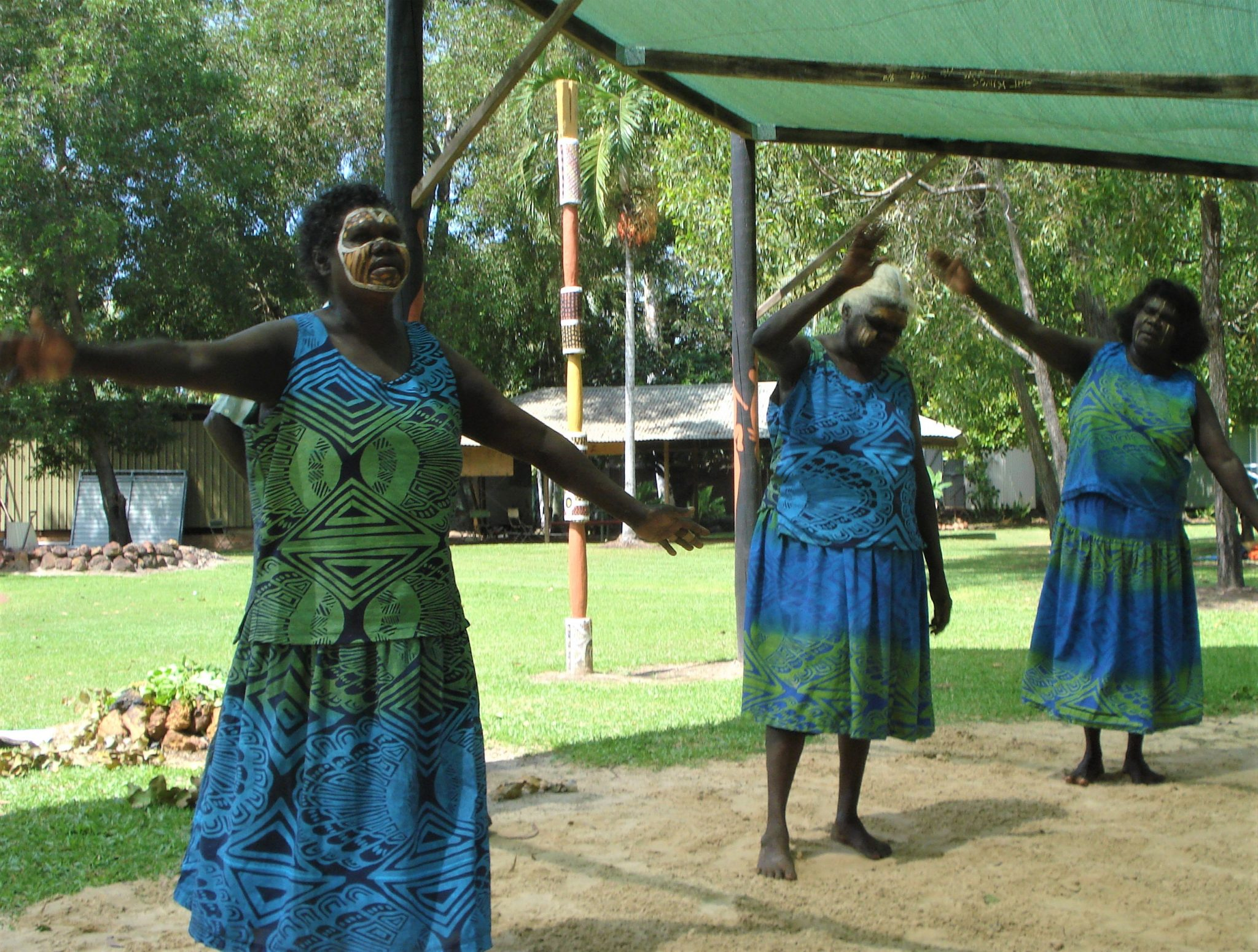 3 Aboriginal women in sleeveless dresses of green, blue and black, dancing under a canopy in a clearing in the jungle of the Tiwi Islands