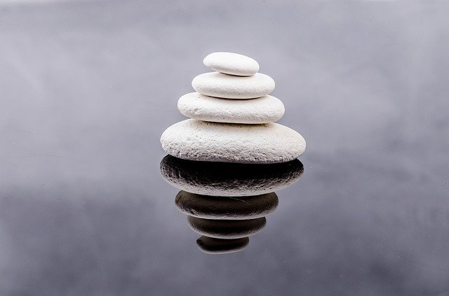 Four white stones balancing on a pool of water with black reflections