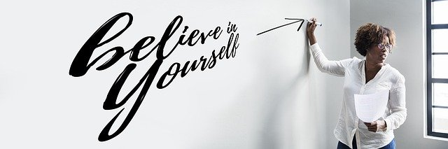 Woman standing next to the phrase believe in yourself written on a wall