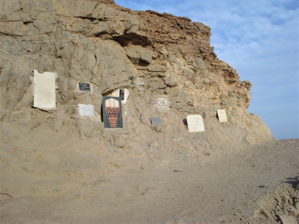 Memorial tombstones on the side of a cliff at the Blue Hole in South Sinai, Egypt