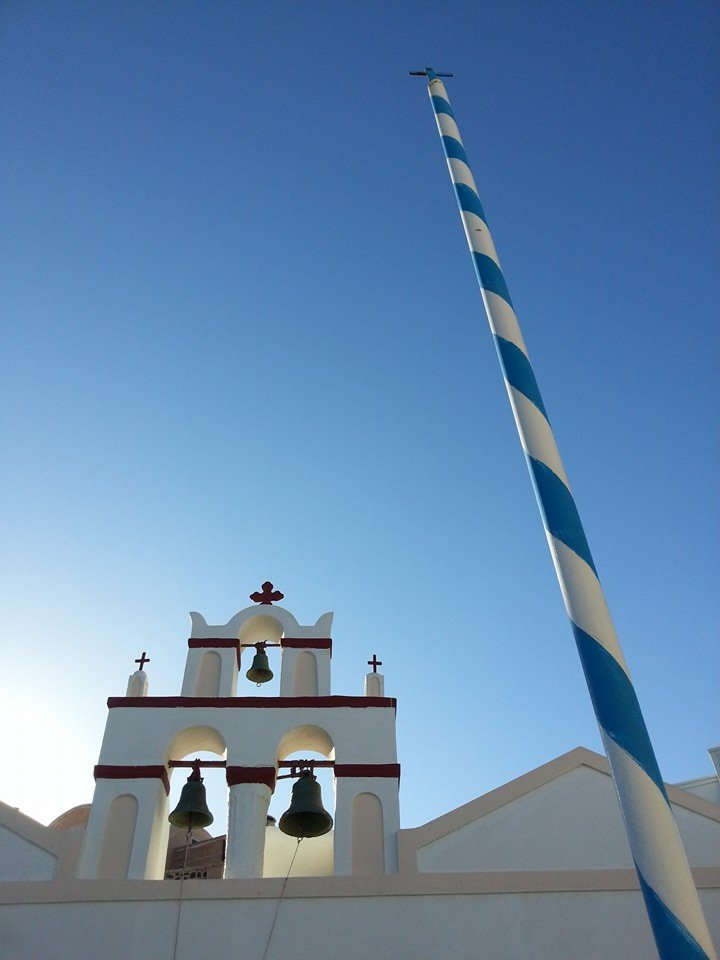 Blue and white striped pole in front of a white church in Santorini, Greece