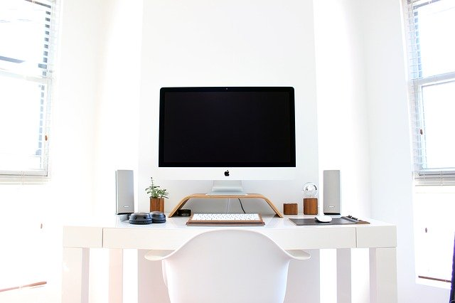 Apple Desktop On Top Of A White Desk With White Chair And A Few Items On The Desk