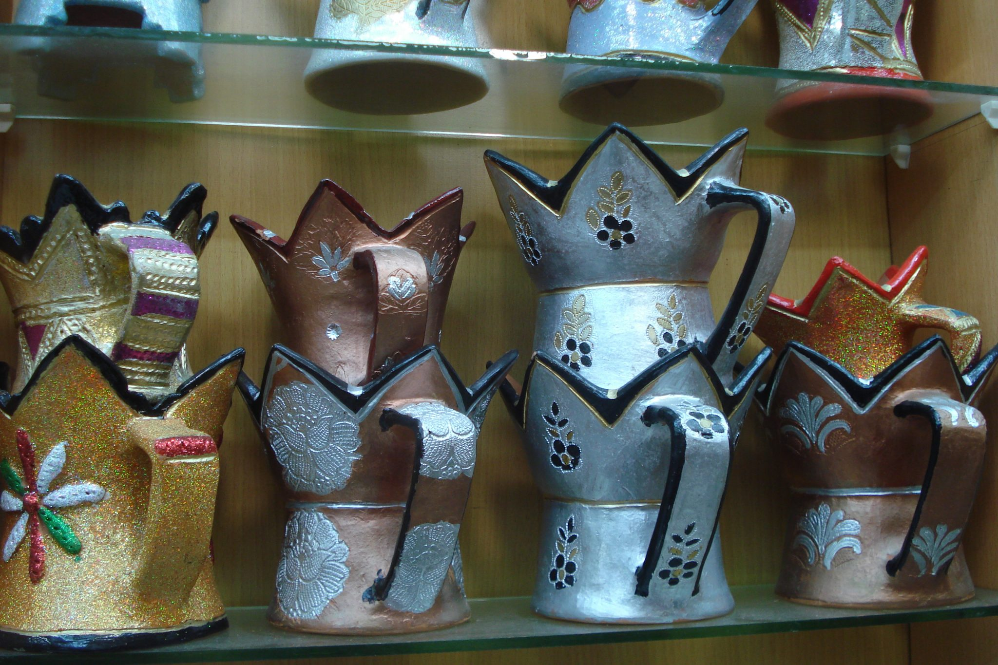 Eight frankincense burners of gold, silver and bronze colors on a glass shop shelf in a souq in Salalah, Oman