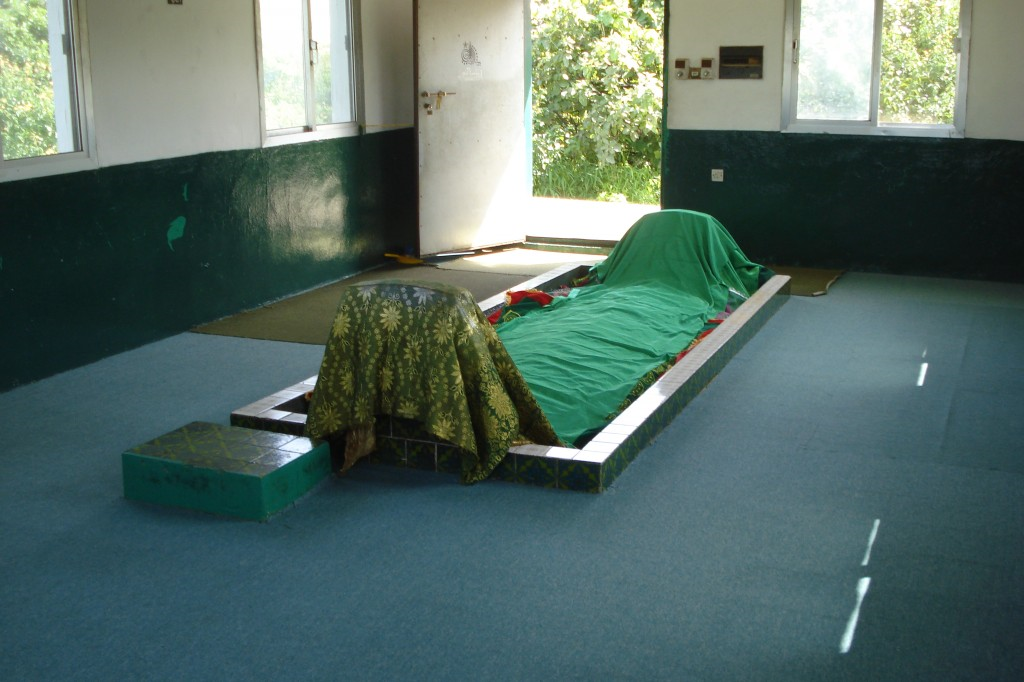 The grave of Job from the Bible is covered in green cloth and is in the middle of a small room with thin blue carpeting, any windows, a door and nothing else in it