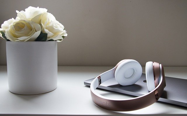 Headphones on top of a closed laptop alongside a white vase with white flowers