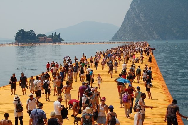 Hundreds of peole on a boardwalk in the middle of water