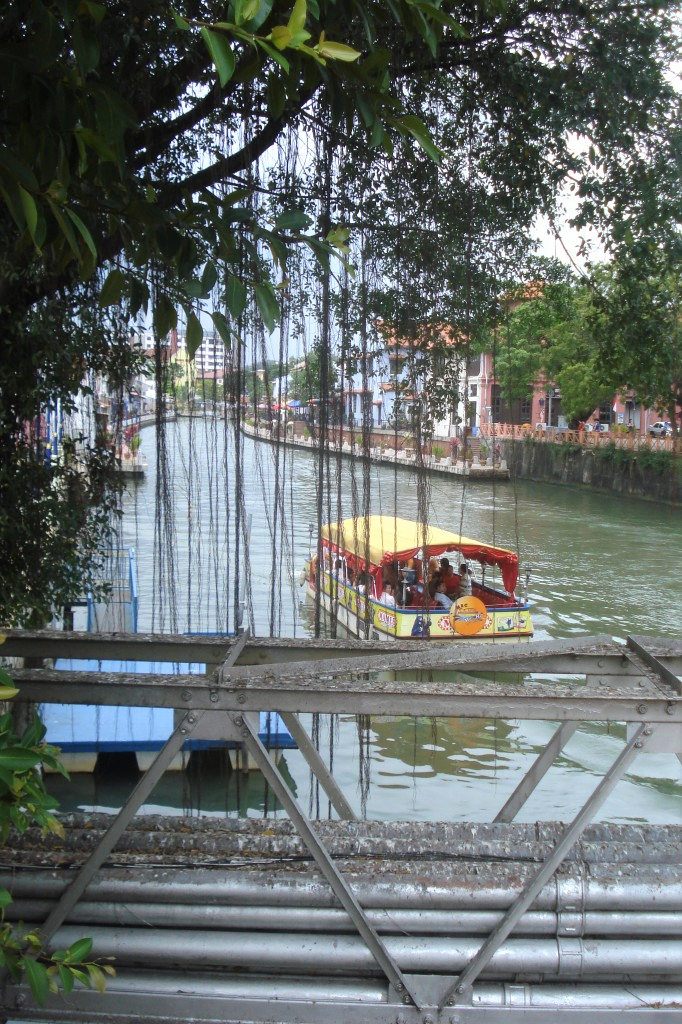 Plants dangling from a tree partially obscuring the view of a yellow riverboat sailing down the Malacca River