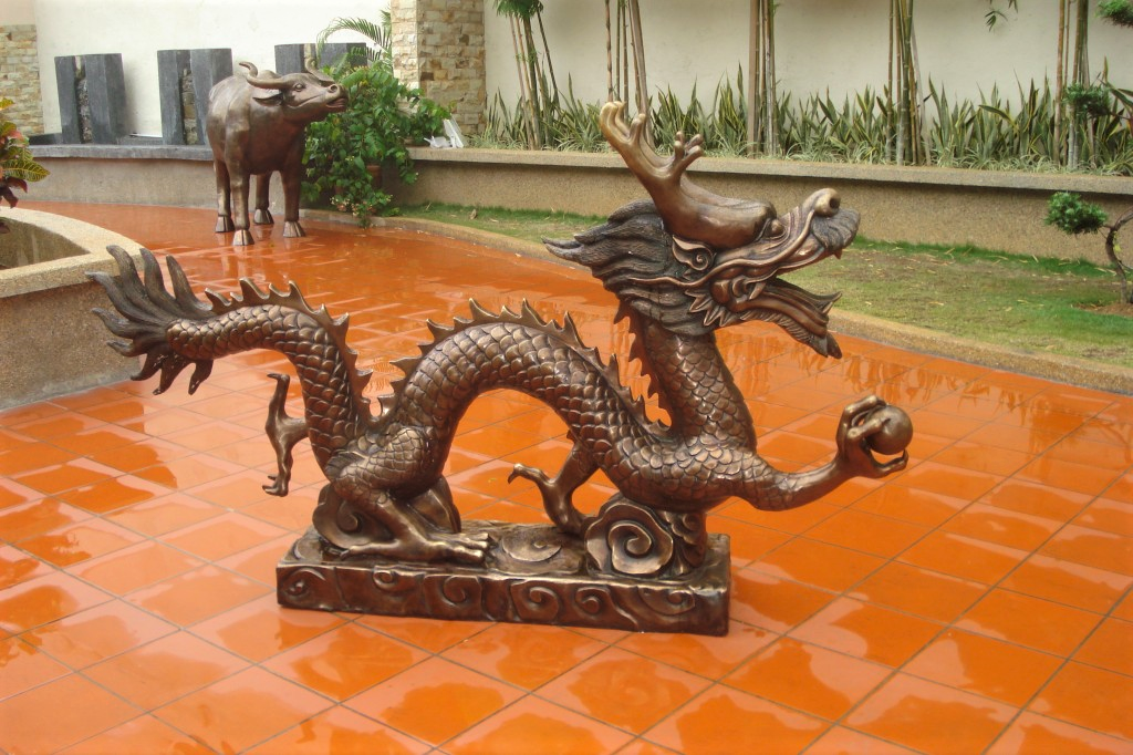 Brass statue of a dragon on orange pavement with a brass statue of a bull in the background