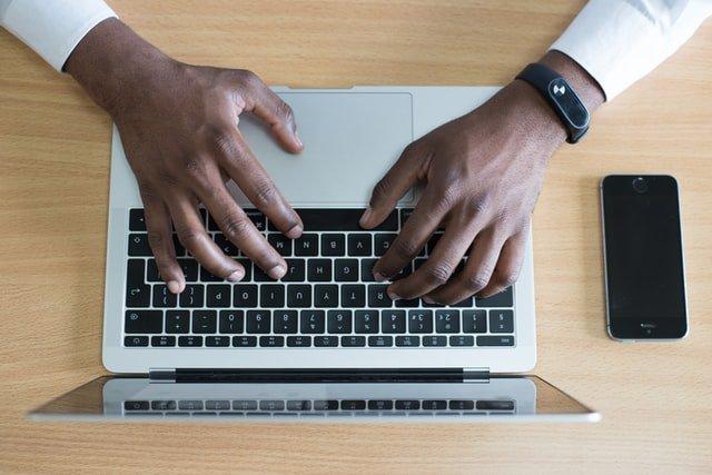 Man's hands on laptop keyboard taking free online courses