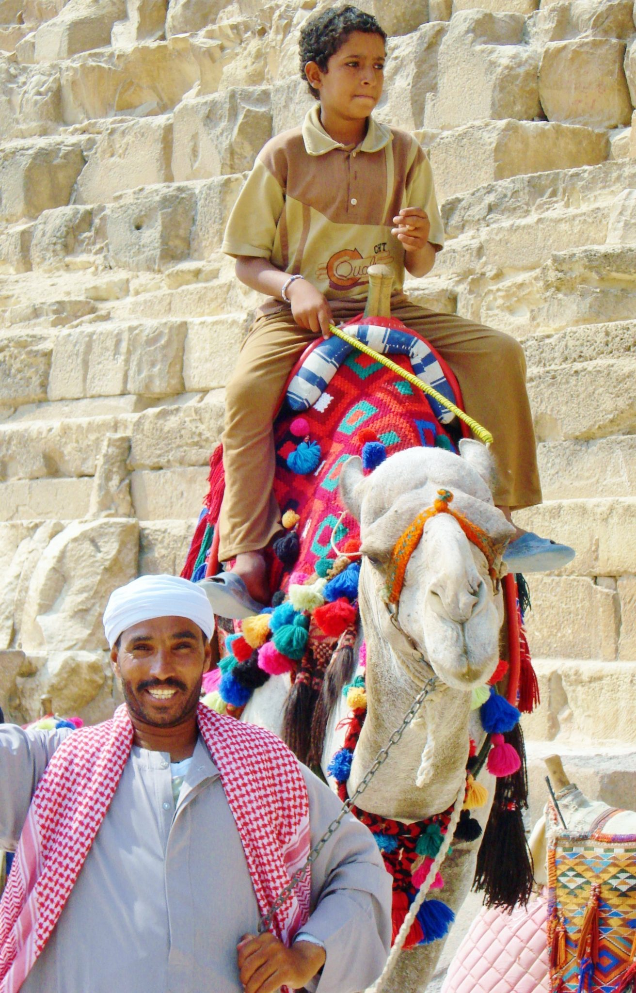 Boy on a colorfully decorated camel with a man standing next to him smiling at the camera in front of a pyramid in Giza, Egypt