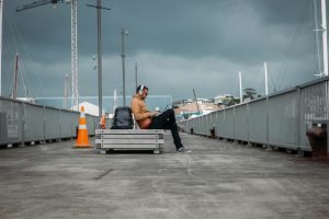 Man listening to headphones on bench while traveling and working