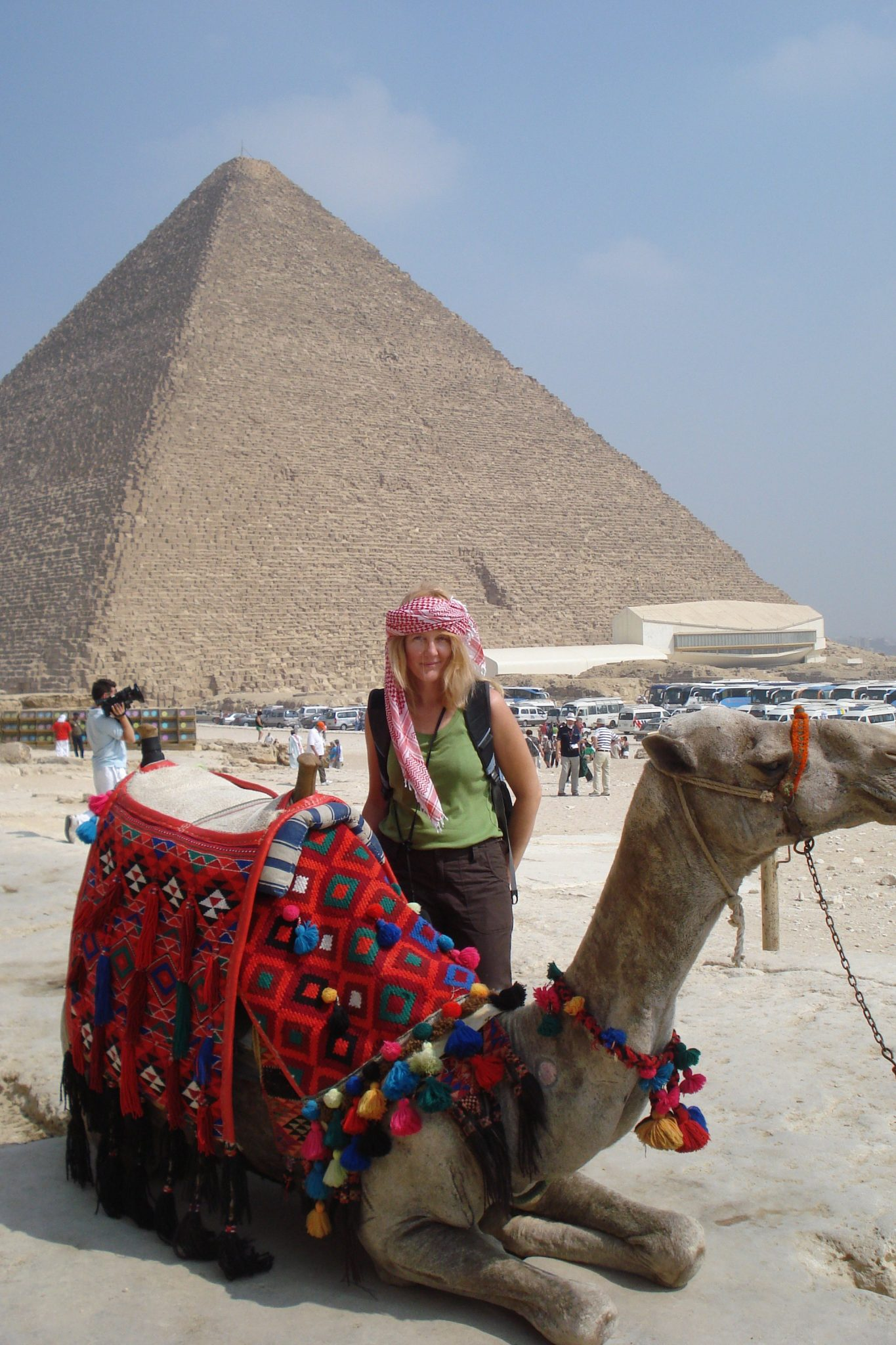 Me wearing a red and white checkered headdress standing behind a colorfully decorated camel in front of the Giza pyramids