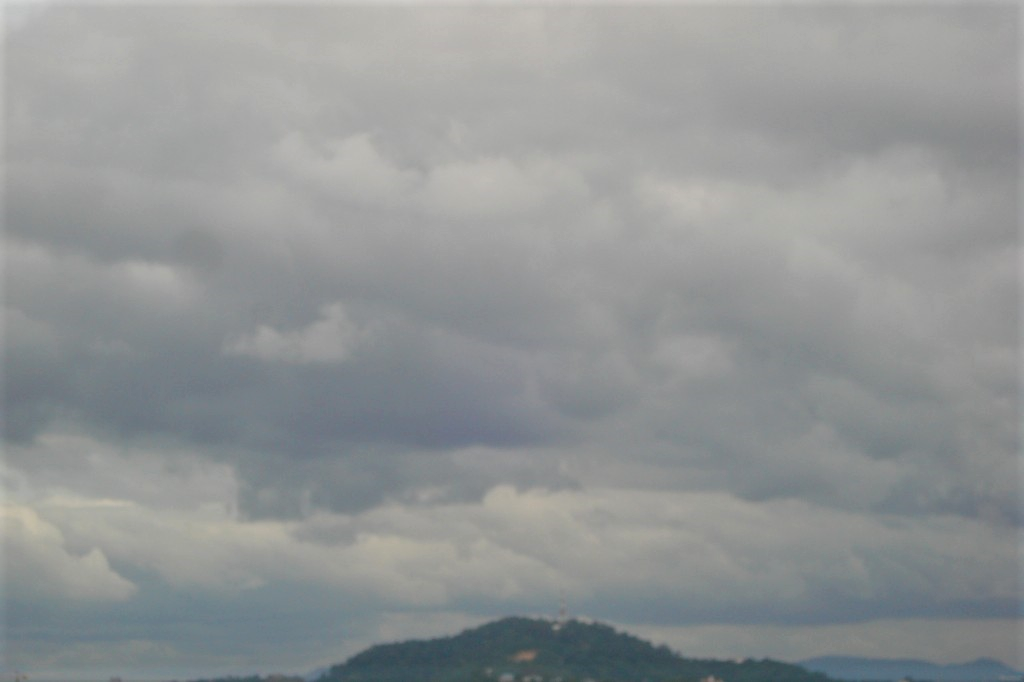 Sky completely filled with very dark clouds atop a mountain