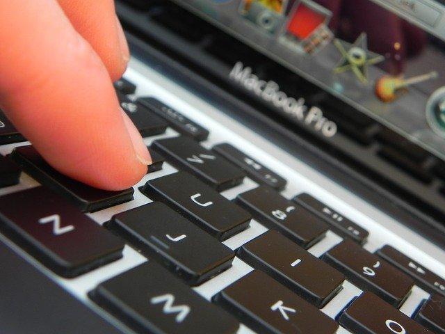 Finger on keyboard of MacBook Pro