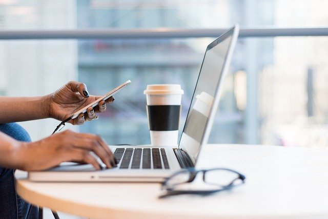 Woman working on multiple streams of income ideas on her laptop and phone