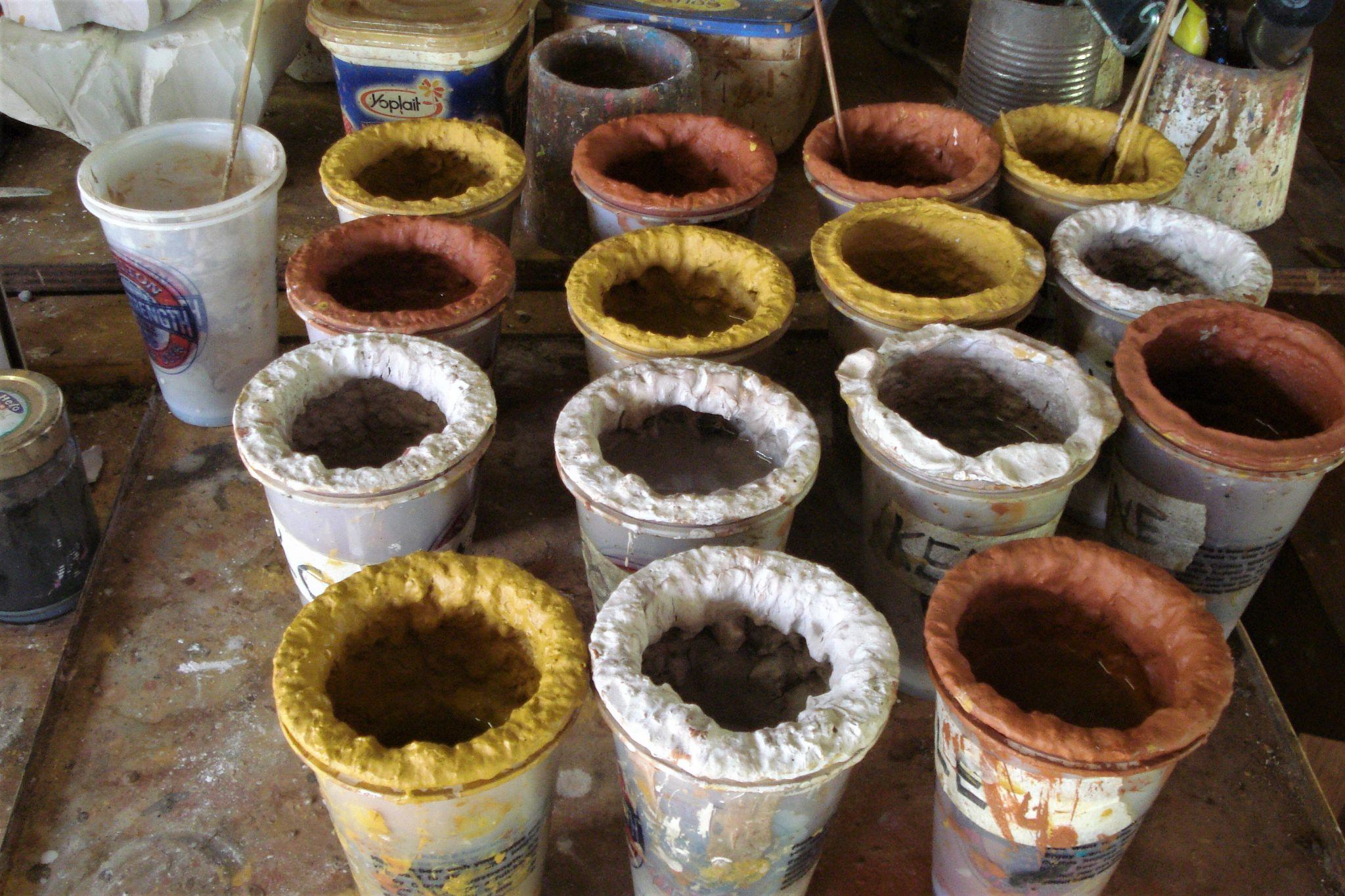 Several buckets of white, yellow and orange ochre paint sitting on a table on my Tiwi Islands day tour