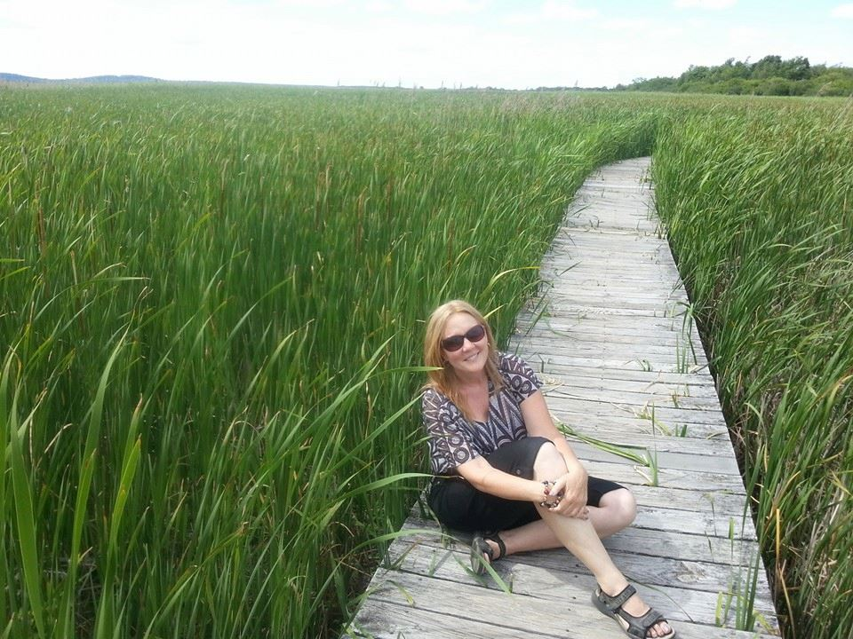 Woman sitting on wooden path in grass while working and traveling