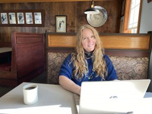 Sabina of World of Freelancers sitting at a table in a restaurant with her laptop and a cup of coffee.