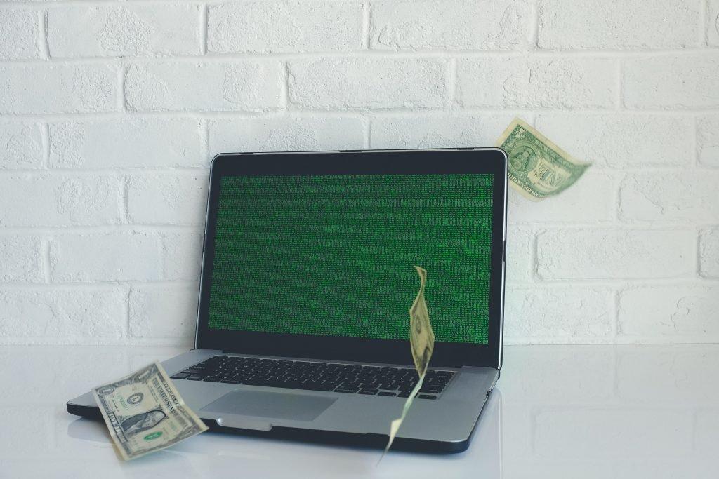 Scopist laptop with dark green screen and three one-dollar bills floating around it
