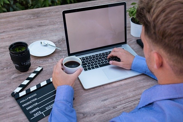 Man starting your own business at laptop with cup of coffee on a table