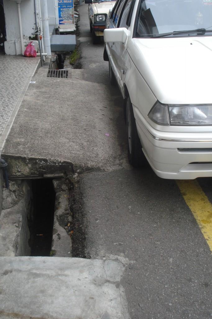Draining ditch along a sidewalk next to a car