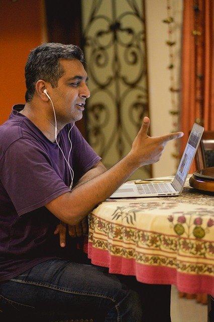 Man teaching ESL online at his kitchen table