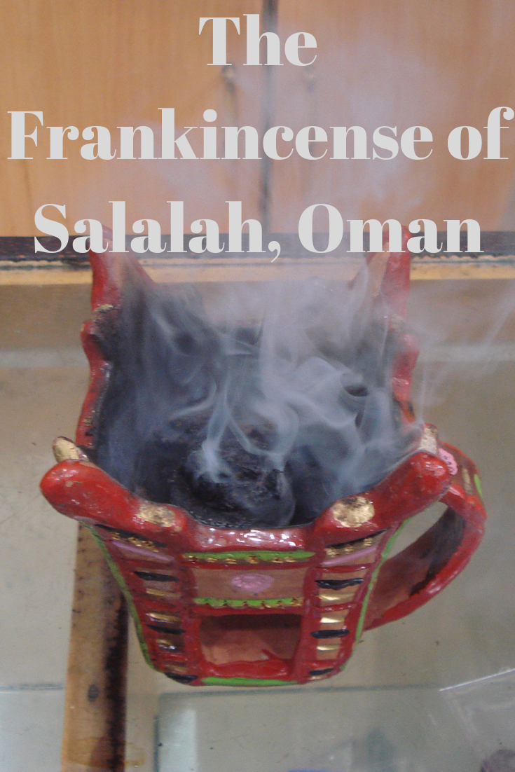 Smoke rising from frankincense burning in a red burner