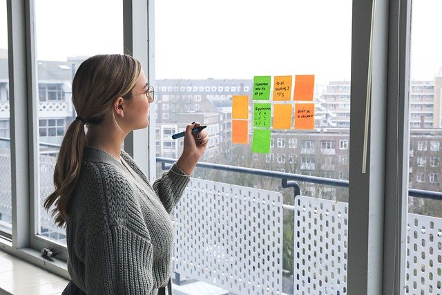 Woman thinking about advice for entrepreneurs and standing at large windows with post-it notes on them