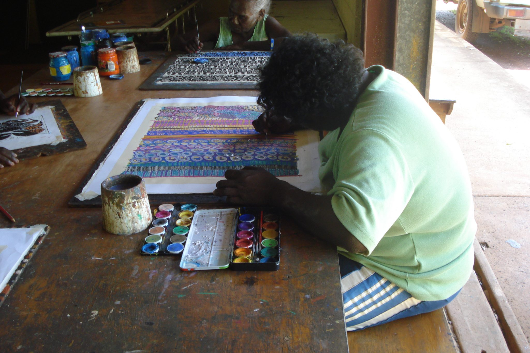 Aboriginal woman in a light green T-shirt painting a colorful canvas on the Tiwi Islands