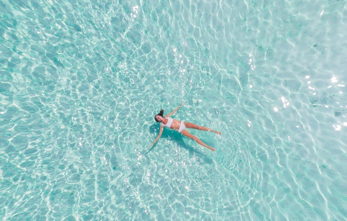 Woman floating in water for a digital detox