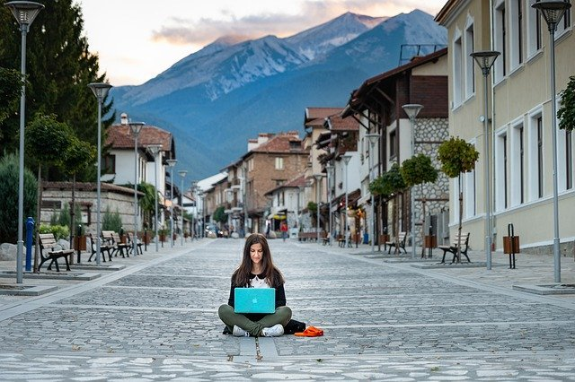 Woman Who Travels And Works Sitting In The Middle Of An Empty Road Lined With Buildings And Mountains In The Background, Working On Her Laptop