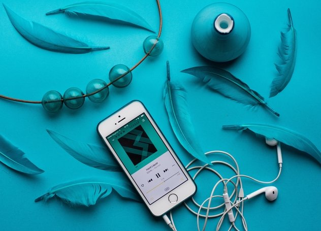 iPhone and earbuds with teal acoutrements with Work at Home podcasts