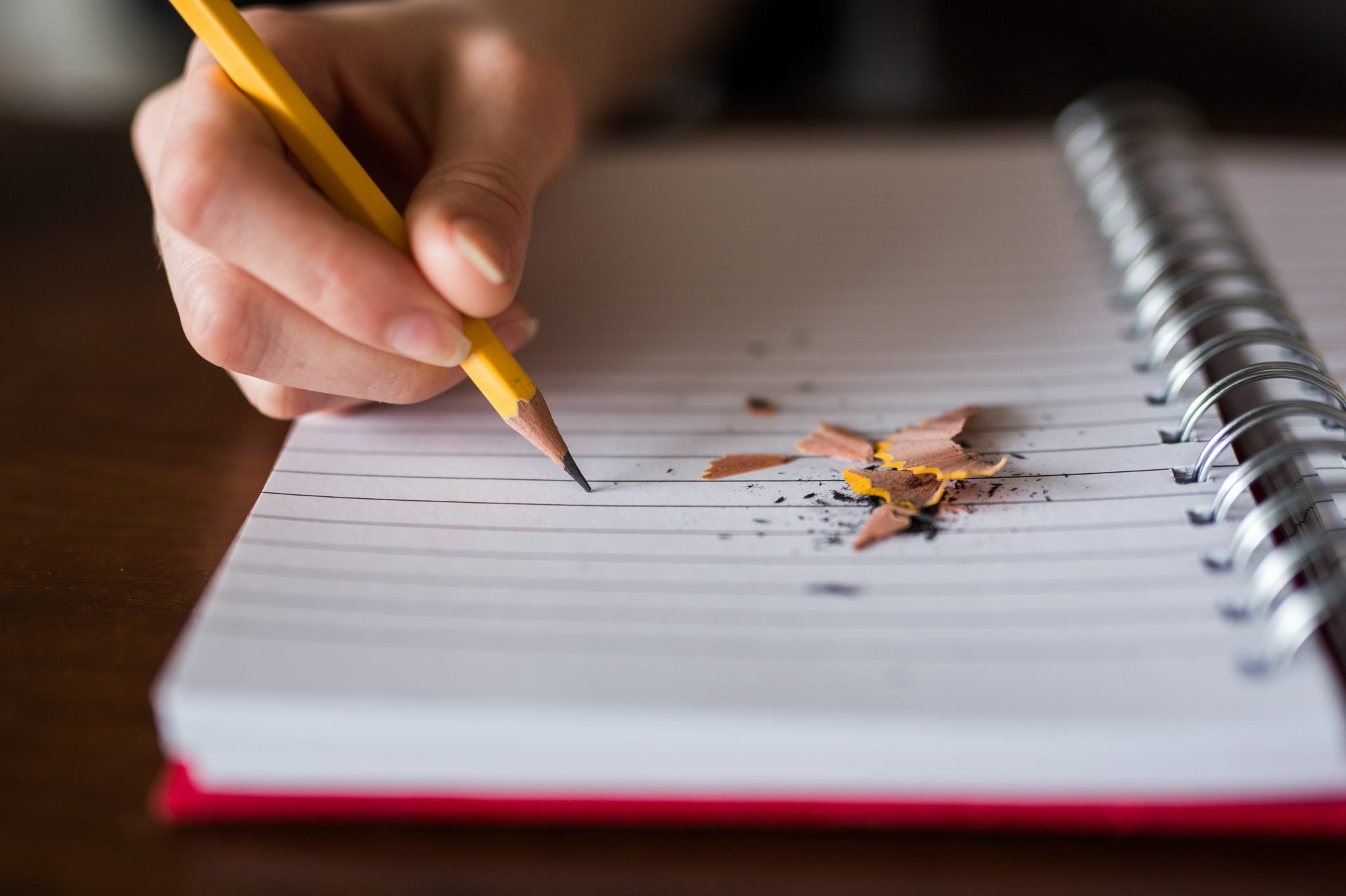 Freelance writer with writer's block needing some writing tips with their hand holding a pencil with pencil shavings on an empty notebook