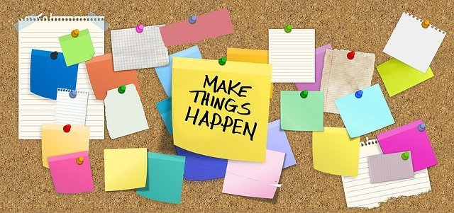 Dozens of colorful Post-It notes on a cork board with the center one saying Make Things Happen, representing the benefits of freelancing