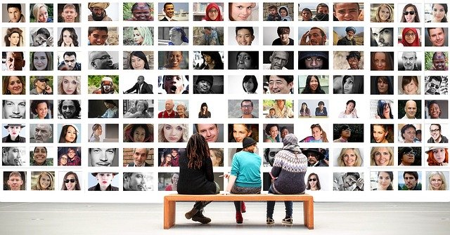 Three people sitting on a bench looking at a wall of headshots of dozens of people
