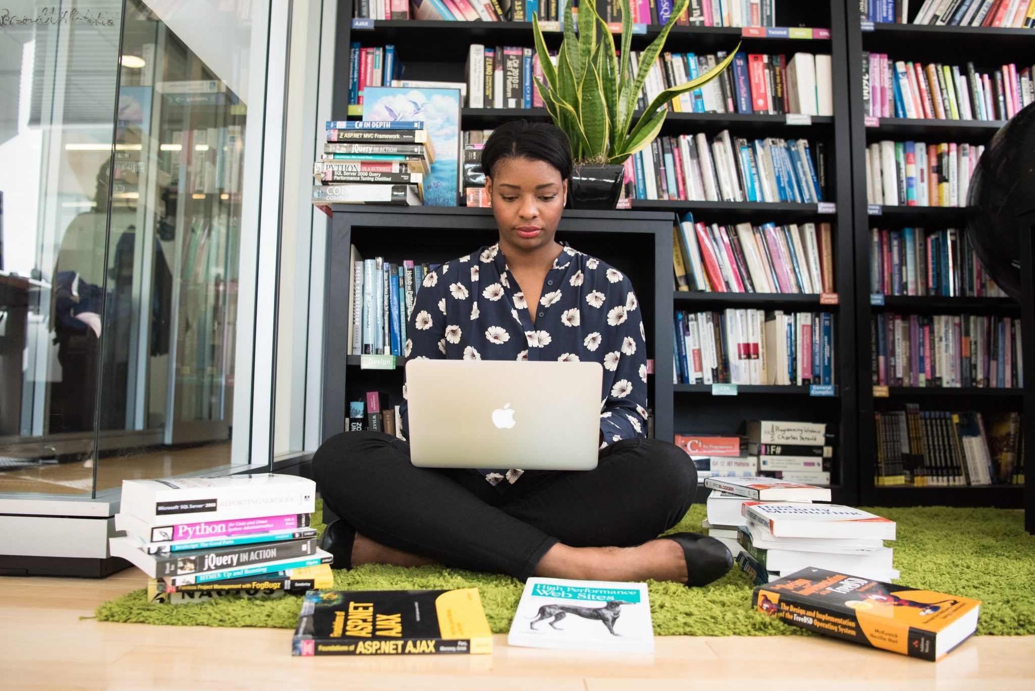 Woman sitting on floor on laptop looking for the best side hustles