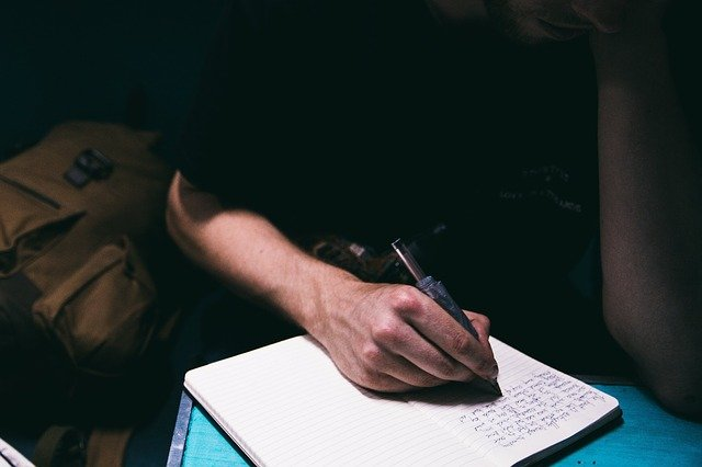 Man's hand holding a pen, writing in his freelance writing notebook