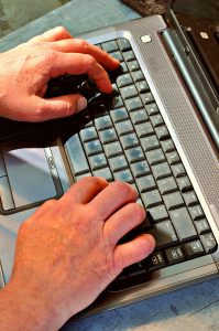 Man's hands on laptop working on a virtual assistant guide