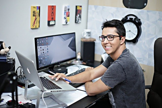 Smiling man working at a desk with two computers