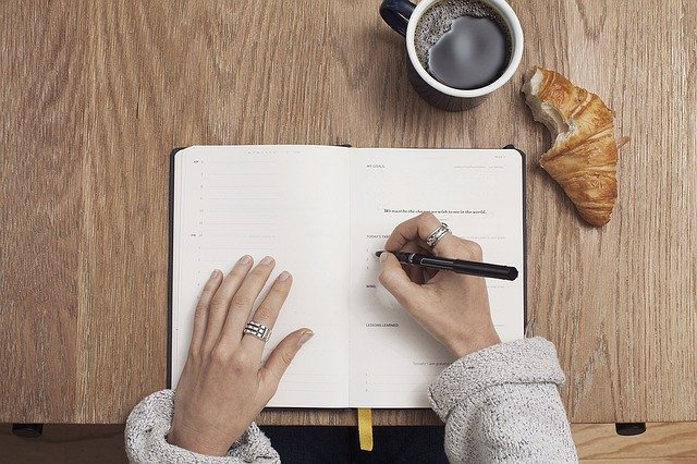 Woman freelancer's hands writing in a notebook, learning how to become a freelance writer