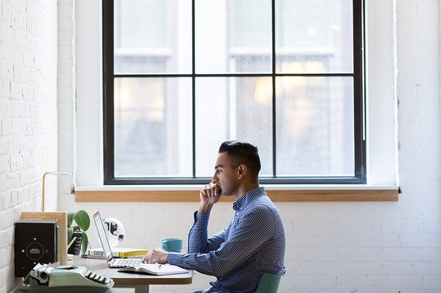 Man working on his multiple income streams sitting at small desk below window