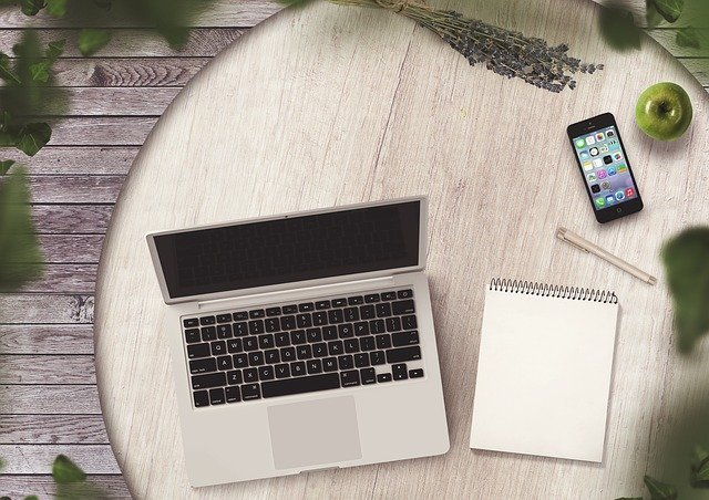 Laptop, notebook, phone and pen for learning how to become a blogger and make money blogging