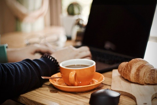 Woman's hands typing on computer with orange cup of coffee and saucer and croissant at her side