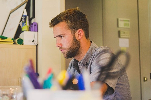 Young man working at desk with office supplies in the foreground