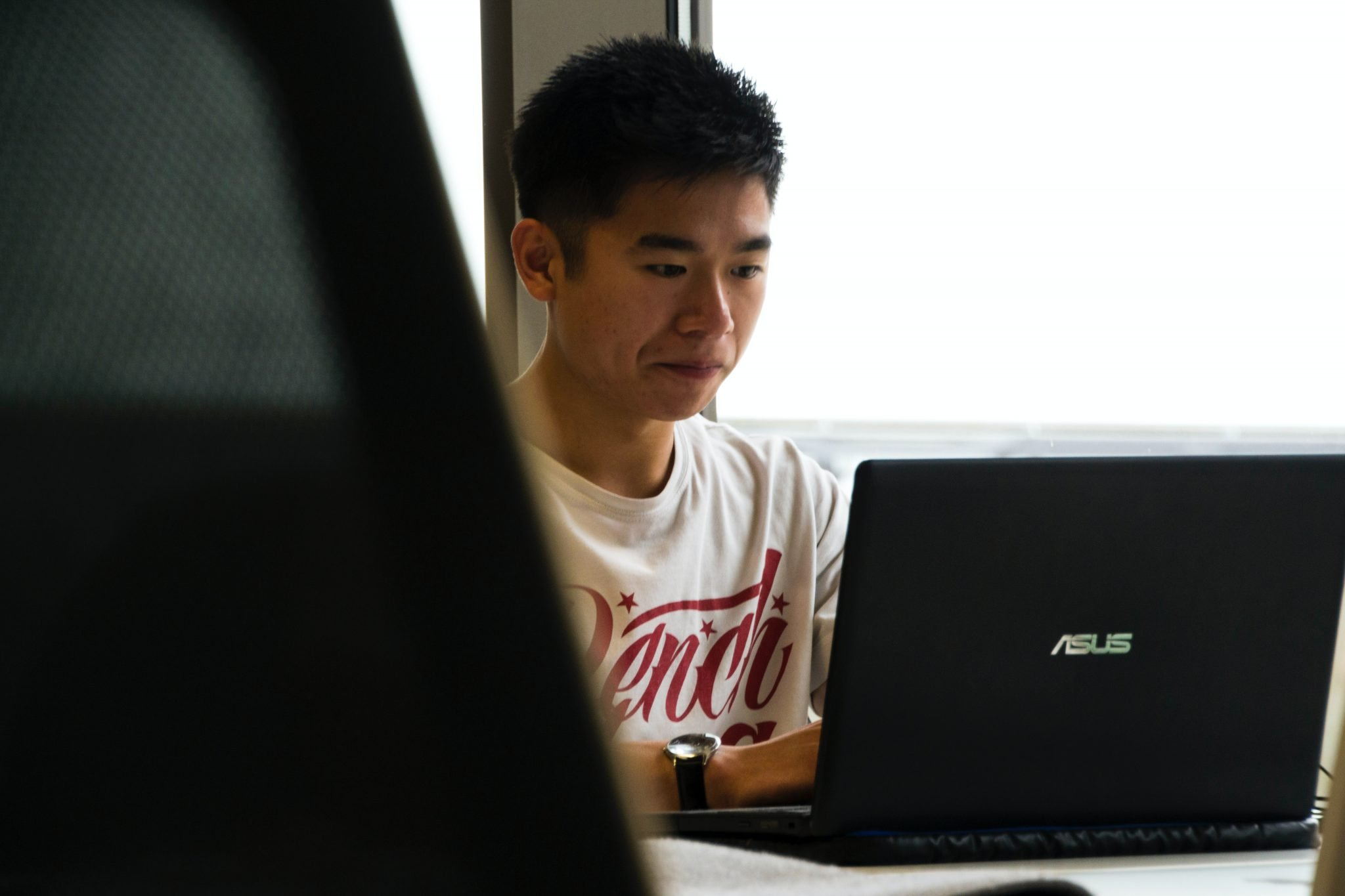 Young man sittinge at his computer reading a virtual assistant guid