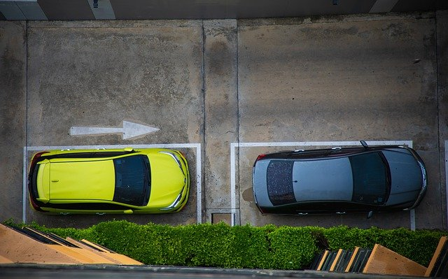 View from above of a yellow car and blue car in parking spaces rented out to earn passive income